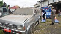 Petugas Satpol PP menarik mobil dinas yang tak kunjung dikembalikan sejumlah mantan pejabat Pemprov Jambi. (Liputan6.com/B Santoso)