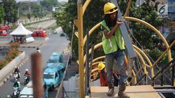 Pekerja menyelesaikan pembangunan Jembatan Penyebaran Orang (JPO) Pasar Minggu di Jakarta Selatan, Kamis (26/9/2019). JPO berdesain artistik senilai Rp 7 miliar tersebut ditargetkan rampung pengerjaannya pada Desember 2019 mendatang. (Liputan6.com/Immanuel Antonius)