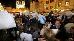 Sejumlah warga saat megambil bagian dalam flash mob perang bantal selama empat menit di Old Town Square di Praha,Ceko (22/12). flash mob perang bantal ini dilakukan jelang pergantian akhir tahun. (REUTERS/ David W Cerny)