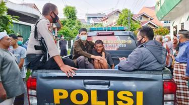 Personel Polsek Tampan membawa pelaku penyerangan imam di sebuah masjid di Pekanbaru.