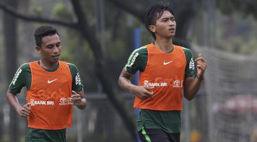 Pemain Timnas Indonesia U-22, Jayus Hariono dan Syafril Lestaluhu, melakukan pemanasan saat latihan di Lapangan ABC, Jakarta, Senin (14/1). Latihan ini merupakan persiapan jelang Piala AFF U-22. (Bola.com/Vitalis Yogi Trisna)