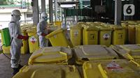 "Petugas menyemprotkan cairan disinfektan pada ""Wheeled Bin"" atau tempat sampah berisi limbah B3 medis Infeksius Covid-19 usai dimusnahkan dengan mesin incinerator di PT Jasa Medivest, Karawang, Jawa Barat, Kamis (10/12/2020).  (Liputan6.com/Herman Zakharia)"