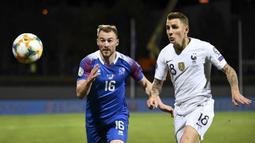 Gelandang Islandia, Runar Mar Sigurjonsson, beradu cepat dengan bek Prancis, Lucas Digne, pada laga Kualifikasi Piala Eropa 2020 di Reykjavik, Sabtu (11/10). Islandia kalah 0-1 dari Prancis. (AFP/Jonathan Nackstrand)
