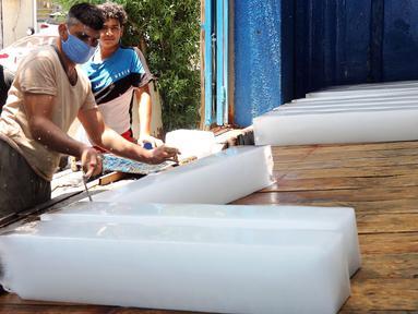 Seorang pekerja memotong balok es di sebuah pabrik pembuatan es di Baghdad, Irak, pada 5 Juli 2020. Seiring kenaikan suhu yang mendekati 50 derajat Celsius di Baghdad, bisnis pembuatan es di kota tersebut berkembang pesat dengan meningkatnya permintaan balok es. (Xinhua)