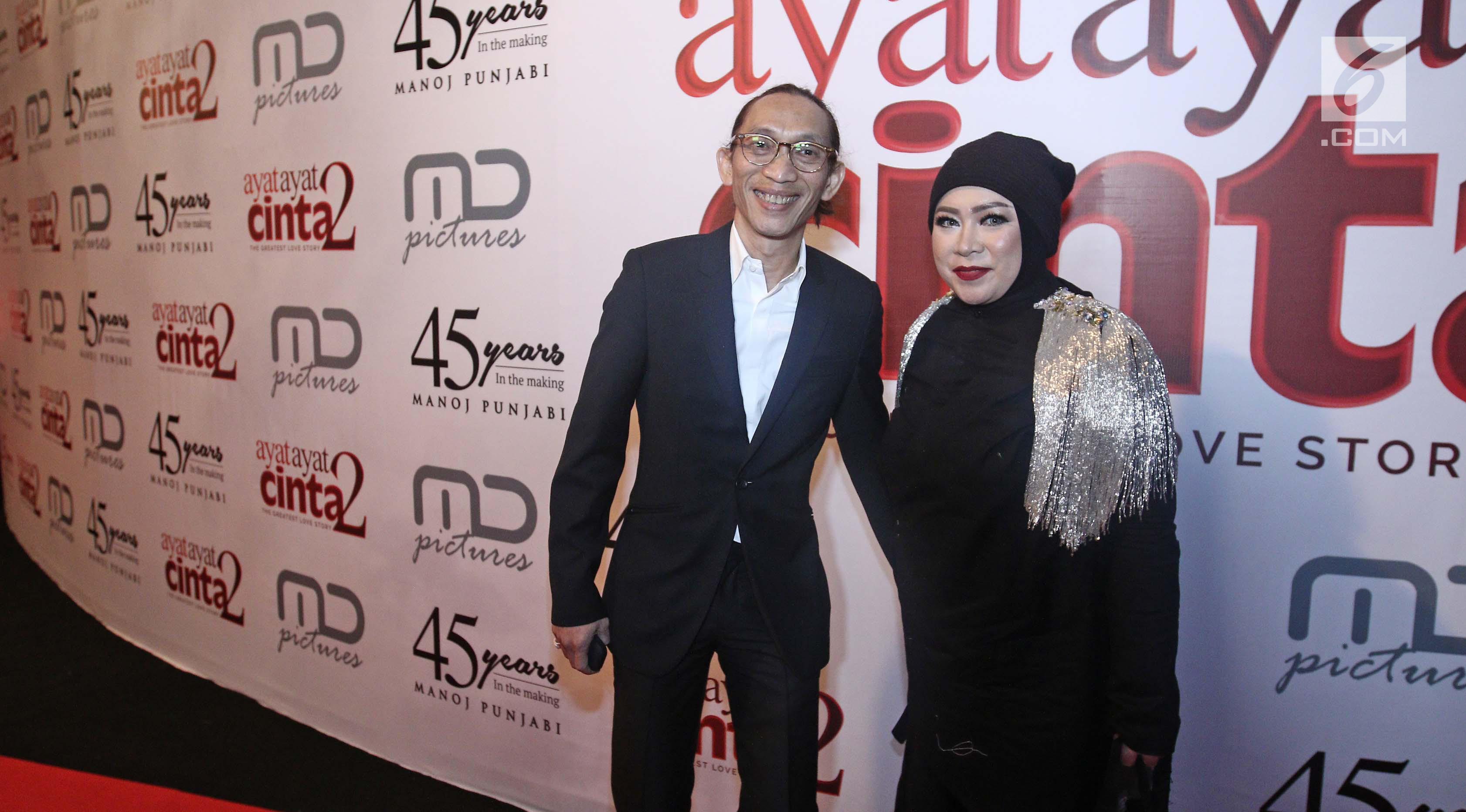 Melly Goeslaw dan suaminya, Anto Hoed berpose untuk difoto saat menghadiri gala premiere film Ayat Ayat Cinta 2 di Jakarta, Kamis (07/12). (Liputan6.com/Herman Zakharia)