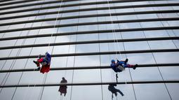 Tokoh superhero Captain America dan Superman membersihkan kaca jendela kamar di rumah sakit anak-anak di Guadalupe, Meksiko, 30 April 2019. Mereka bergelantungan di luar jendela dengan mengenakan kostum superhero untuk menghibur anak- anak yang sedang sakit. (REUTERS/Daniel Becerril)