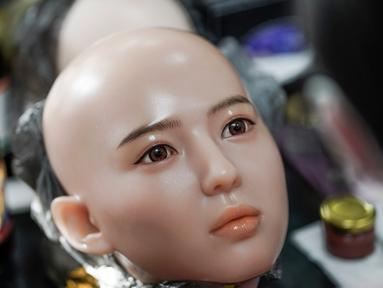Seorang pekerja melukis wajah boneka seks di sebuah pabrik yang terletak di Dalian, China, Kamis (1/2). Pabrik boneka seks ini ingin menghubungkan orang-orang yang kesepian dan pensiunan dengan jenis pendamping baru. (AFP PHOTO/FRED DUFOUR)