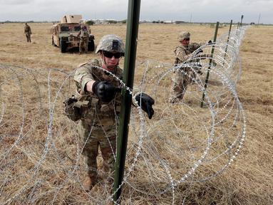 Tentara AS memasang kawat duri dekat jembatan perbatasan antara AS dengan Meksiko di Donna, Texas, Minggu (4/11). Presiden AS Donald Trump mengatakan kehadiran pasukannya untuk mengantisipasi 'invasi' imigran. (AP Photo/Eric Gay)