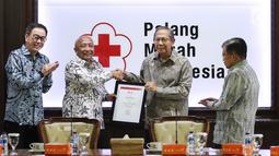 Plh Ketum PMI Ginandjar Kartasasmita memberikan penghargaan kepada Astra International yang diwakili Chief of Corcomm, Social Responsibility & Security Astra International Pongki Pamungkas di Kantor PMI, Jakarta, Jumat (8/2). (Liputan6.com/Fery Pradolo)