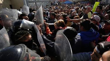 Anggota keluarga terlibat bentrok dengan polisi yang memblokir pintu masuk penjara Topo Chico, di Monterrey, Meksiko, Kamis (11/2). 52 orang tewas dan 12 lainnya terluka dalam kerusuhan di penjara yang terjadi menjelang fajar itu (REUTERS/Daniel Becerril)