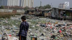 Seorang anak terlihat di dekat permukiman kumuh yang berdiri di atas tumpukan sampah di Kampung Bengek, Jakarta Utara, Selasa (3/9/2019). Permukiman kumuh ini berdiri di atas rawa yang membeku karena timbunan sampah plastik, kasur bekas hingga limbah rumah tangga. (Liputan6.com/Faizal Fanani)