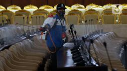 Petugas melakukan penyemprotan cairan disinfektan di area ruang rapat paripurna di Gedung Nusantara, Kompleks Parlemen MPR/DPR-DPD, Senayan, Jakarta, Minggu (29/3/2020). Penyemprotan disinfektan ini juga untuk mencegah penyebaran wabah corona (Covid-19). (Liputan6.com/Johan Tallo)