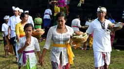 Umat Hindu membawa sesajen menuju pura untuk sembahyang Hari Raya Galungan di Jimbaran, Bali, Rabu (5/4). Galungan dirayakan oleh umat hindu di Bali sebagai hari kemenangan Dharma (Kebaikan) melawan Adharma (Keburukan). (SONNY TUMBELAKA/AFP)