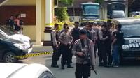 Polisi berjaga setelah pelaku bom bunuh diri meledakkan dirinya di Mapolrestabes Medan, Sumatera Utara, Rabu (13/11/2019). Area Mapolrestabes Medan dijaga ketat aparat kepolisian bersenjata lengkap. (Rahmad SURYADI/AFP)
