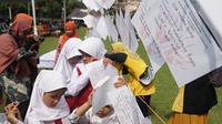 Para siswa-siswi SD SLBN A Kota Bandung membaca kertas braille berisi harapan terhadap sekolahnya pada acara peringatan Hari Disabilitas Internasional, Jumat (6/12/2019). (Liputan6.com/Huyogo Simbolon)