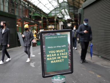 Tanda yang memberitahu pengunjung untuk memakai masker dipasang di pintu masuk Borough Market di London selatan selama penguncian nasional (lockdown) ketiga Inggris, Selasa (12/1/2021). Borough Market menjadi tempat pertama yang mewajibkan pemakaian masker di luar ruangan. (AP Photo/Alastair Grant)