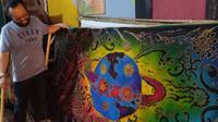 Anto Gondrong menunjukkan hasil lukisan batik motif Covid-19 hasil karyanya. (foto: Siti Hardiani)