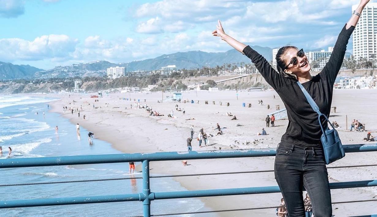 Paula sering tampil menggunakan busana berwarna hitam saat liburan. Saat berlibur di Pantai Santa Monica, ia tampak bahagia menggunakan baju dan celana jeans berwarna hitam ditemani dengan tas berwarna biru. (Liputan6.com/IG/@paula_verhoeven)