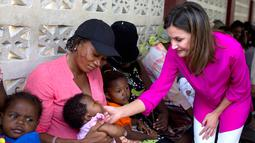 Ratu Spanyol Letizia menyapa seorang bayi perempuan dalam kunjungannya ke rumah sakit di daerah kumuh Soleil, Haiti, 23 Mei 2018. Ini merupakan kunjungan pertama Ratu Letizia ke negara termiskin di benua Amerika tersebut. (AP/Dieu Nalio Chery)