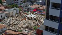 Petugas penyelamat menggali tumpukan puing-puing setelah sebuah bangunan runtuh di Fortaleza, negara bagian Ceara, Brasil, Selasa (15/10/2019). Pejalan kaki yang tengah melewati gedung ketika runtuh juga dibawa ke klinik medis terdekat. (RODRIGO PATROCINIO / AFP)