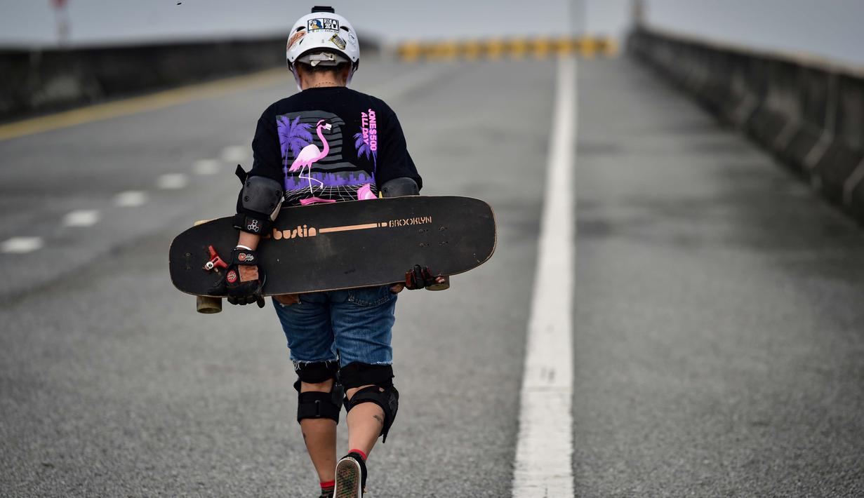 Foto pada 9 September 2020 menunjukkan longboarder dan penderita kanker Nongluck Chairuettichai, juga dikenal sebagai Jeab, selama sesi latihan di jalan raya yang belum selesai di Bangkok. Kegiatan ini dilakukan sebagai jalan pemulihan dari kanker payudara yang dideritanya. (Lillian SUWANRUMPHA/AFP)