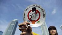 Seorang simpatisan menunjukkan stiker kawasan bebas merokok dalam aksi peringatan Hari Tanpa Tembakau di Bundaran Hotel Indonesia, Jakarta.(Antara)