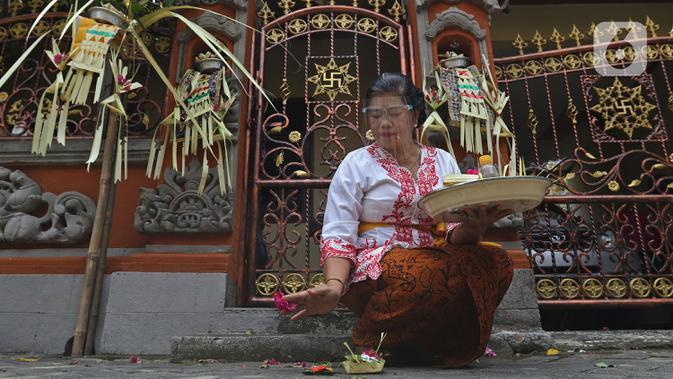 Umat Hindu saat melaksanakan ritual persembahyangan Hari Raya Galungan di Kampung Bali, Bekasi Utara, Jawa Barat, Bekasi, Rabu (16/9/2020). Perayaan hari kemenangan kebenaran (Dharma) atas kejahatan (Adharma) tersebut dilakukan di kediaman masing-masing. (Liputan6.com/Herman Zakharia)