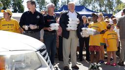 Presiden AS, Donald Trump membawa makanan sebelum dibagikan kepada korban badai Florence di Temple Baptist Church di New Bern, N.C. (19/9). Badai tersebut juga membuat hampir seluruh kota di North Carolina dibanjiri lumpur dan air. (AP Photo /Evan Vucci)
