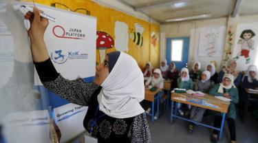 Pengungsi asal Suriah, Omayma Al Hushan saat menulis di hadapan rekan-rekannya mengenai perlawanan terhadap pernikahan di bawah umur di sebuah sekolah di kamp pengungsi Al Zaatari, Mafraq, Yordania (21/4). (REUTERS / Muhammad Hamed)