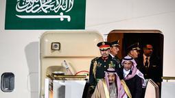 Pengawal membantu Raja Arab Saudi, Salman bin Abdulaziz Al Saud menuruni tangga eskalator saat tiba di Vnukovo International Airport, Rusia, 4 Oktober 2017. Eskalator emas milik Raja Salman macet setelah bergerak beberapa saat. (Alexander NEMENOV/AFP)