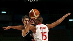 Pemian Argentina, Nicolas Brussino (kiri) berebut bola dengan pemain Kuba, Jasiel Riveroduring dalam Kejuaraan Basket Piala Amerika 2015 di Sport Palace, Meksiko City, Meksiko. (3/9/2015). (Reuters/Henry Romero)