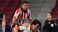 Bek Atletico Madrid, Kieran Trippier (kiri) melompati bek Sevilla, Marcos Acuna saat berebut bola dalam lanjutan Liga Spanyol 2020/2021  di Stadion Wanda Metropolitano, Madrid, Spanyol, Rabu (13/1/2021) dini hari WIB. Atletico Madrid membungkam Sevilla dengan skor 2-0. (PIERRE-PHILIPPE MARCOU/AFP)