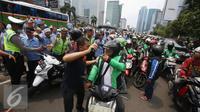 Petugas menenangkan pengadara Go-Jek yang terlibat kericuhan di Jakarta, Selasa (22/3). Ratusan Go-Jek mendatangi para sopir taksi karena tersebar isu pemukulan terhadap beberapa pengendara Go-Jek oleh sopir taksi.  (Liputan6.com/Immanuel Antonius)