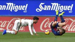 Gelandang Real Madrid, Marco Asensio, menjatuhkan bek Eibar. Paulo Oliveira, pada laga La Liga di Stadion Ipurua, Eibar, Sabtu (24/11). Eibar menang 3-0 atas Madrid. (AFP/Ander Gillenea)
