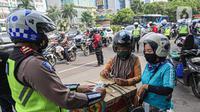 Petugas kepolisian lalu lintas mengecek SIM pengendara motor saat Operasi Zebra Jaya 2020 di kawasan Cawang, Jakarta, Senin (26/10/2020). Operasi Zebra Jaya dilaksanakan pada 26 Oktober-8 November 2020 untuk menekan jumlah pelanggaran lalu lintas. (Liputan6.com/Faizal Fanani)