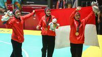 Tim pencak silat seni beregu putri Indonesia, Pramudita Yuristya (kiri), Lutfi Nurhasanah (tengah) dan Gina Tri Lestari (kanan) berselebrasi usai meraih medali emas Asian Games 2018, Jakarta, Rabu (29/8). (ANTARA FOTO/INASGOC/Melvinas Priananda/nak/18)