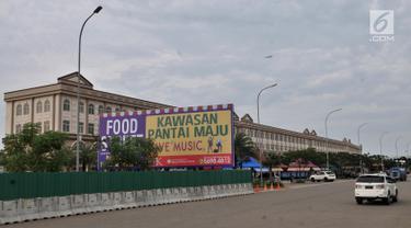 Kendaraan melintas dekat baliho pusat kuliner atau food street di kawasan Pantai Maju yang dahulu bernama Pulau D, Jakarta, Rabu (23/1). Area Food Street di kawasan Pantai Maju mulai beroperasi usai disegel oleh Pemprov DKI. (Merdeka.com/Iqbal S. Nugroho)