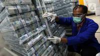 Petugas menata tumpukan uang di Cash Pooling Bank Mandiri, Jakarta, Rabu (20/1/2021). BI mencatat likuiditas perekonomian atau uang beredar dalam arti luas (M2) tetap tinggi pada November 2020 dengan didukung komponen uang beredar dalam arti sempit (M1) dan uang kuasi. (Liputan6.com/Johan Tallo)