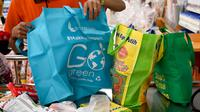 Karyawan mengemas barang belanjaan konsumen dengan tas belanja nonplastik di sebuah supermarket di Denpasar, 16 Juli 2019. Bali menerapkan pelarangan penggunaan plastik sekali pakai yang tertuang dalam Peraturan Gubernur (Pergub) Nomor 97 Tahun 2018. (SONNY TUMBELAKA/AFP)