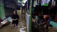 Aktivitas warga saat banjir di Jati Padang, Jakarta Selatan, Kamis (30/11). Banjir yang terjadi tersebut akibat tanggul darurat di Kali Pulo jebol karena genangan air yang cukup deras dan membanjiri permukiman sekitar. (Liputan6.com/Johan Tallo)