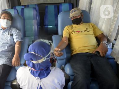 Petugas Palang Merah Indonesia (PMI) mengambil darah pendonor di mobil donor darah keliling, Tangerang Selatan, Banten, Jumat (17/7/2020). PMI mengintensifkan pengoperasian mobil donor darah keliling untuk memenuhi persediaan stok darah saat pandemi COVID-19. (merdeka.com/Dwi Narwoko)