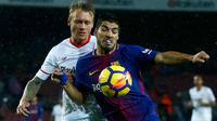Penyerang Barcelona, Luis Suarez berusaha membawa bola dari kawalan pemain Sevilla, Simon Kjaer saat bertanding pada lanjutan La Liga Spanyol di Camp Nou, Barcelona, Spanyol, (4/11). Barcelona menang 2-1 atas Sevilla. (AP Photo/Manu Fernandez)