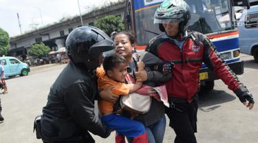 Seorang wanita dan anaknya terjaring razia oleh petugas Dinsos DKI di Kawasan Terminal Kampung Melayu, Jakarta, Jumat (11/5). Razia dilakukan dalam rangka jelang bulan Ramadan. (Liputan6.com/Arya Manggala)