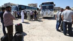 Warga Suriah dari provinsi Idlib, berkumpul sebelum menaiki bus ke Tanah Suci Makkah di kota Binnish, Senin (22/7/2019). Jemaah calon haji asal Suriah melakukan perjalanan ke Arab Saudi untuk menjalankan ibadah haji dari perbatasan Bab al-Hawa yang berseberangan dengan Turki. (Omar HAJ KADOUR/AFP)