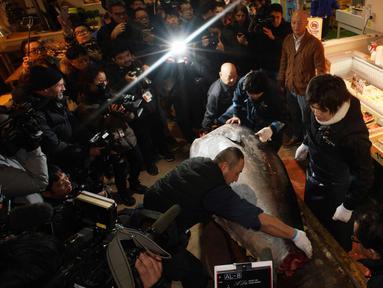 Pekerja pedagang grosir Yamayuki memotong tuna sirip biru seberat 405 kilogram yang mereka jadikan tawaran kemenangan pada pelelangan pertama tahun ini, di dekat pasar ikan Tsukiji di Tokyo, Jepang (5/1). (AP Photo / Eugene Hoshiko)
