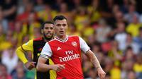 Gelandang Arsenal, Granit Xhaka berusaha mengontrol bola dibayangi pemain Watford pada pekan kelima Liga Inggris 2019-2020 di Vicarage Road, Minggu (15/9/2019). Sempat unggul dua gol, Arsenal harus rela imbang 2-2 saat berjumpa tim tuan rumah Watford. (Ben STANSALL / AFP)