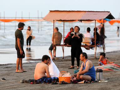 Warga Iran beristirahat sambil menikmati suasana di pantai di kota Laut Kaspia, Izadshahr, provinsi Mazandaran utara (8/7/2019). Laut Kaspia terletak di antara Eropa dan Asia, di sebelah barat dan barat-daya pegunungan Ural. (AFP Photo/Atta Kenare)