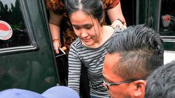 Jessica Kumala Wongso, tersangka kasus pembunuhan Wayan Mirna Salihin, turun dari mobil tahanan kejaksaan, di Rutan Pondok Bambu, Jakarta, Jumat (27/5). Jessica tetap bungkam saat akan dibawa masuk ke penjara khusus wanita itu. (Liputan6.com/Yoppy Renato)
