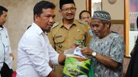 Ketua PWI Garut Ari Maulana Karang disaksikan Wakil Bupati Garut Helmi Budiman, memberikan paket sembako bagi warga Garut, dalam bakti sosial rangkain HPN di Garut. (Liputan6.com/Jayadi Supriadin)