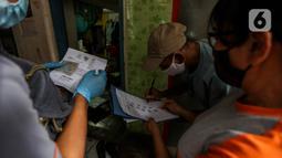 Warga penerima bantuan menandatangani bukti pemberian bantuan sosial tunai (BST) di RW 05 Kelurahan Kenari, Senen, Jakarta, Rabu (6/1/2021). Pencairan bantuan senilai Rp 300 ribu dilakukan dengan tiga cara, salah satunya diantar langsung ke rumah secara door to door. (Liputan6.com/Johan Tallo)